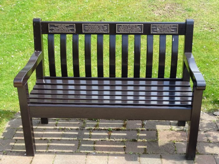 A bench with various memorial plaques on the back rest