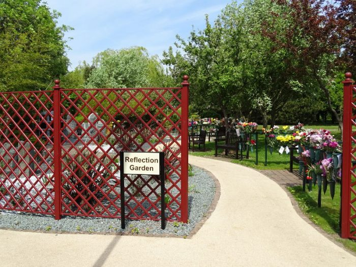 Entrance to the reflection garden, showing a sign and path through benches and flowers